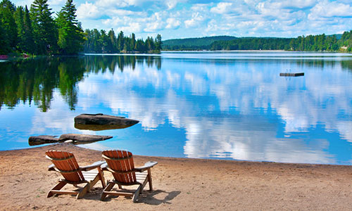 Two Muskoka chairs on a beach in front of a beautiful blue lake