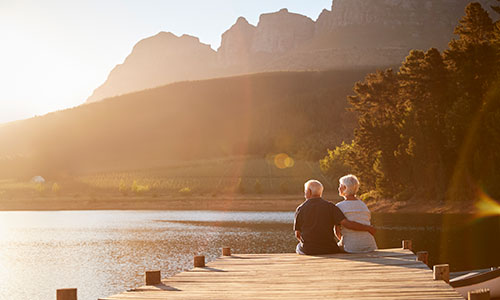 Couple sitting on the end of a dock looking out over a lake with mountains in the background