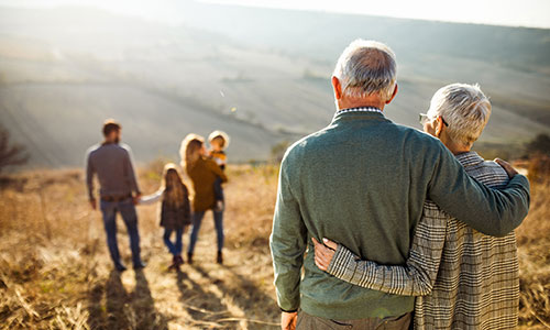 Senior couple watching a family of four walk down a mountain path in front of them