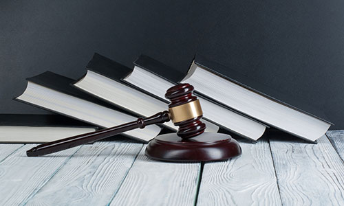 Gavel sitting in front a five books