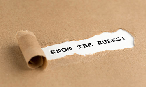 """A piece of brown paper is ripped on rolled back to reveal the words """"Know the Rules!"""""""
