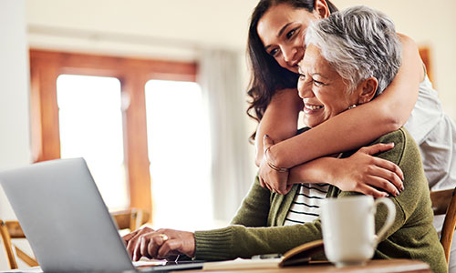 Woman hugging her mother while the mother uses the computer