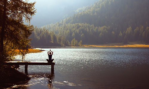 Woman practising yoga at the end of a dock on a lake in a mountain valley